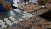 Thailändische Verkäufer, die Kanom Babin auf einer heißen Bratpfanne kochen