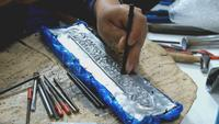 Craftsman using tool carving Thai pattern on metal plate