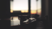 A record player spinning while the sun is setting