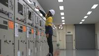 Technician Pressing Buttons on Electrical Pannel