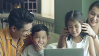 Familia asiática feliz mirando a la computadora portátil.