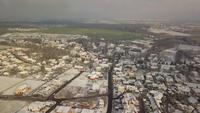 Drohne fliegt über schneebedecktes Dorf in 4K