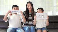 Woman and her kids show a sign stay home