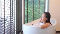 Asian woman relaxing in bathtub