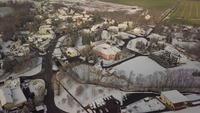Drone in een baan om een besneeuwd kasteel in een dorp in 4K