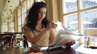 Frau, die eine Zeitung in einem Cafe liest