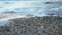 Wellen brechen an einer Küste mit kleinen Steinen