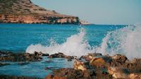 Zeegolven die op rotsen verpletteren