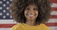 Mujer sonríe con bandera americana