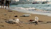 As pessoas andam na praia com resíduos de plástico