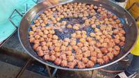 Gens faisant frire des boulettes de poisson dans l'huile chaude
