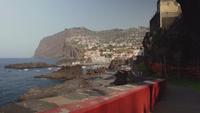 Wandelen langs de promenade met een stad in de verte, Madeira, Portugal