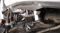 Le mécanicien répare la suspension du train de roulement et les pièces d'essieu d'une voiture