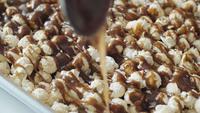 Verter caramelo se derrite sobre las palomitas de champiñones