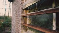 Prikkeldraad en metalen staven voor een oud raam