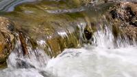 El agua que fluye sobre las rocas hacia una piscina natural.