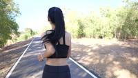 Der Rücken einer Frau, die in einem Park läuft