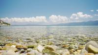 Lugnt havsvatten som träffar de små stenstenarna på stranden.