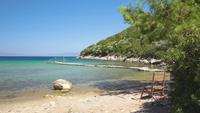 Houten stoelen op een prachtig strand in Samos, Griekenland.