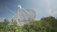 A radiotelescope hidden behind the trees