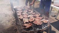 Dos hombres asando carne en la barbacoa