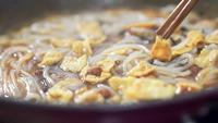 Lecker Nudeln und Tofu mit Stäbchen mischen