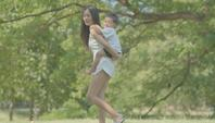 Jovem mãe asiática brinca com seu filho no parque