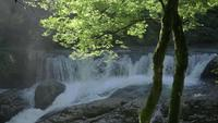 Câmera lenta de uma cachoeira com raio de sol