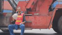 Frachtcontainerarbeiter, der am Arbeitsplatz ruht