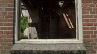 Panning through a window at an abandoned building