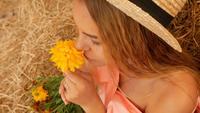 De jonge vrouw die een bloem houdt en snuift het