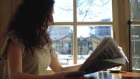 La mujer se sienta cerca de una ventana y lee un periódico