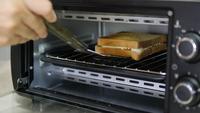 Persona saca un sándwich cocido del horno casero