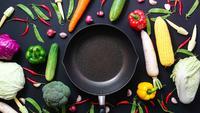 Bovenaanzicht stop motion groenten en een pan op zwarte achtergrond.
