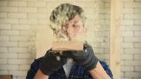Joven sopla el aserrín de una pieza de madera en el taller