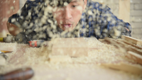 Young Carpenter Blows Sawdust in The Workshop