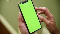 Frau, die Smartphone mit grünem Bildschirm verwendet