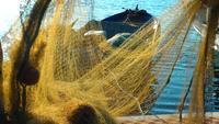 Pescador repara redes de pesca e linhas de pesca