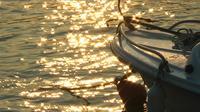 Fischerboot und Sonnenreflexion auf Meerwasser