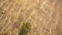 Mar limpo sobre areia e seixos