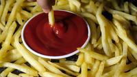 Hand som doppar pommes frites i tomatsås