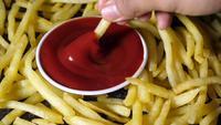 Mäns hand doppar pommes frites i tomatsås