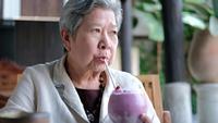 Älterer Senior, der einen Blaubeermilchshake trinkt