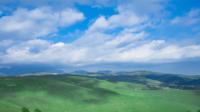 Paysage de montagne verte avec des collines et des nuages