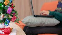 Kvinna som arbetar från hennes soffa under jul