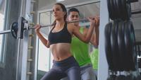 Sportlerin, die mit Unterstützung eines Personal Trainers trainiert