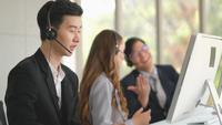 Telefoniste werkt terwijl zijn collega's praten en lachen