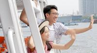 Tourist Couple Waving to Other People During Boat Trip