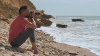 Homem sentado à beira-mar com uma câmera