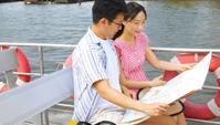 Ein Paar, das auf der Terrasse eines Touristenboots sitzt und eine Karte betrachtet